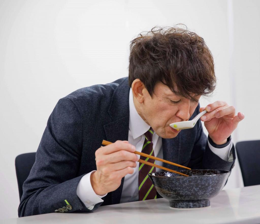『雲丹らーめん』を試食している折茂 武彦氏